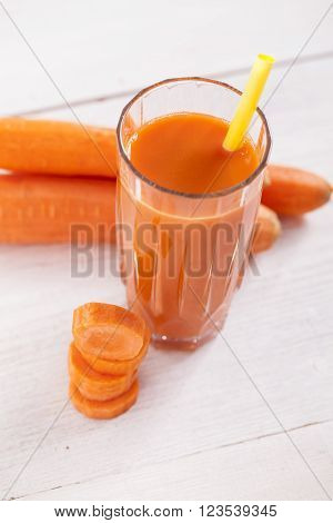 Fresh carrot juice in glass on wooden table