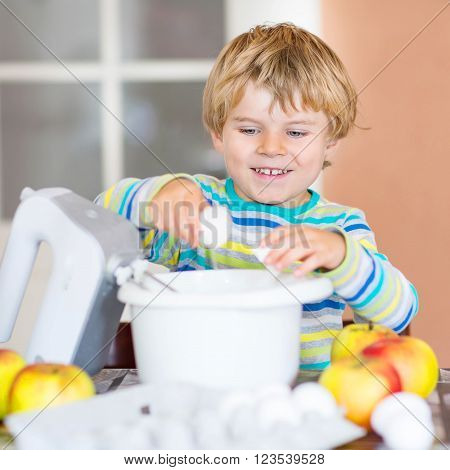 Cute adorable blond kid boy baking apple cake in domestic kitchen. Happy child having fun with working with mixer, flour, eggs and fruits.
