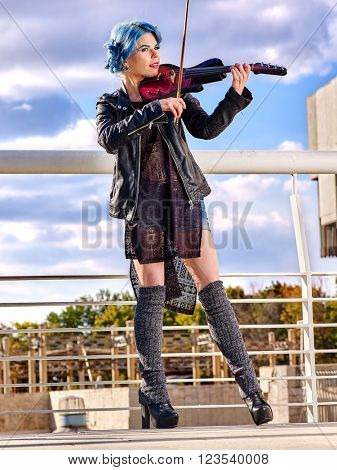 Music street performers slim girl violinist with blue hair playing  aganist sky with clouds outdoor. Urban landscape.
