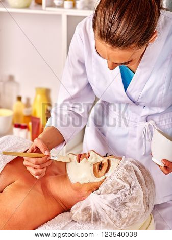 Woman middle-aged take facial and neck clay mask in spa salon. Two female people. Care of health.