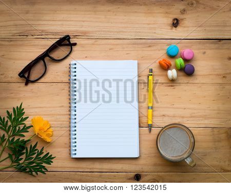 Blank Notebook And A Yellow Pen With Hot Coffee And Colorful Sweet On  Wooden Table In Warm Tone.