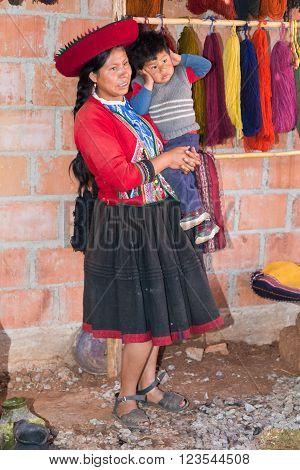 Ollantaytambo, Peru - Circa June 2015: Women In Traditional Peruvian Clothes Holds A Boy Near Cusco,