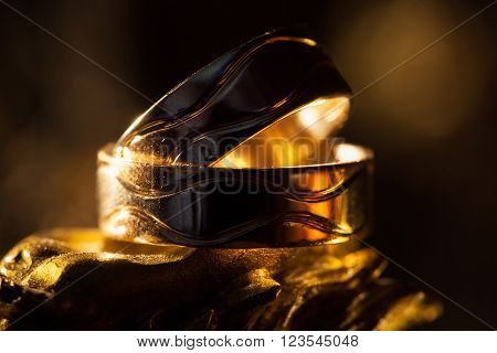 Wedding rings in the rays of yellow light.