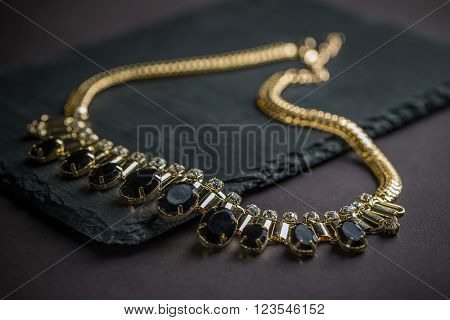 Necklace with gems on black background, studio shot