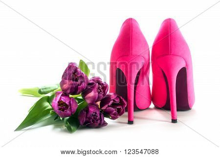 Ladies pink high heel shoes from behind and tulips isolated with shadows on a white background, concept symbol for love, valentines, mothers day and womens day, copy space, selected focus
