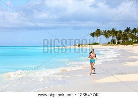 Fitness runner woman running on tropical white sand beach nature landscape outdoors. Beautiful nature in Caribbeans with person jogging living a healthy lifestyle for weight loss in summer.