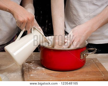 The process of kneading dough. human hands Close. The dough is made of flour. Cookware - red pot, white pitcher. Hand poured water from a jug