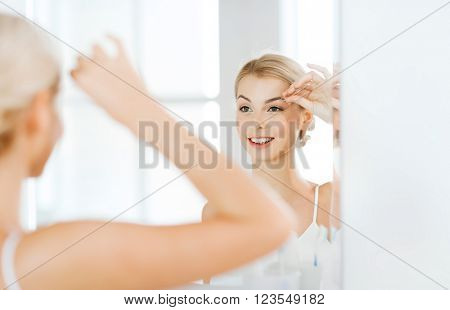 beauty and people concept - smiling young woman with tweezers tweezing eyebrow and looking to mirror at home bathroom