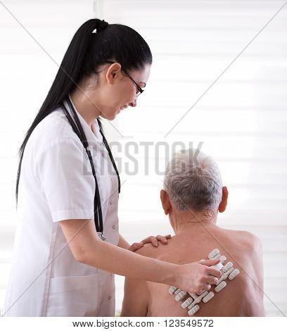 Nurse Masagging Old Man With Roller Massager