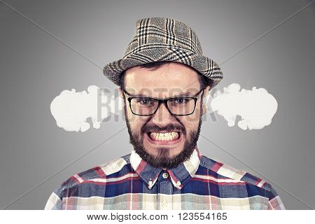 angry young man blowing steam coming out of ears