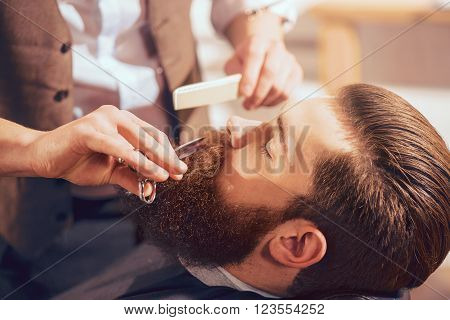Crafty hands. Handsome man sitting in the barbershop  while professional barber holding scissors and cutting his beard