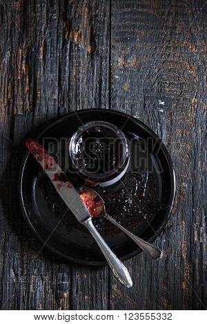 The top view of fruity jam and spoon and knife on black wooden table
