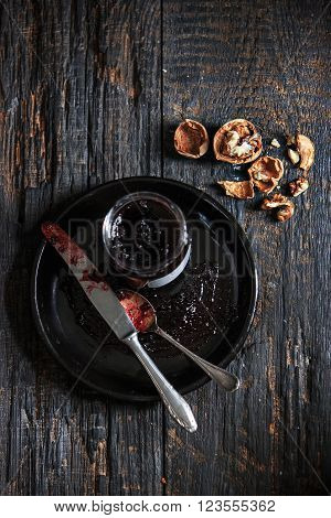 The top view of fruity jam and spoon and knife on black wooden table with walnuts