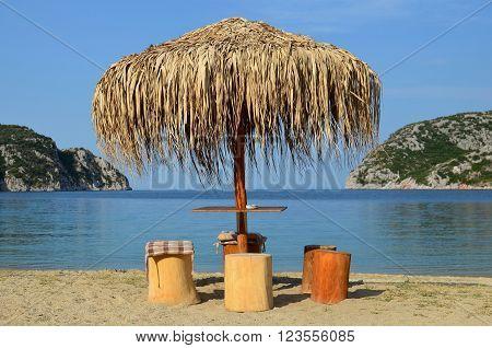 Sun umbrella and stump seats on sandy beach next to entrance of Porto Koufo harbour on south end of Sithonia Greece
