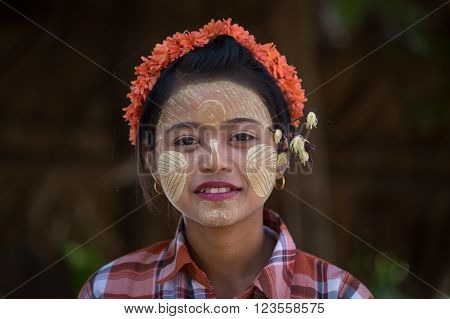 MANDALAY MYANMAR - JANUARY 17 2016: Unidentified young Myanmar girl with thanaka on her smile face is happiness. Thanaka is a yellowish-white cosmetic paste made from ground bark.