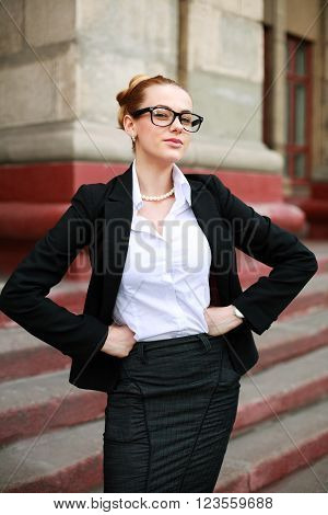 Serious girl student in a business suit in front of a university building