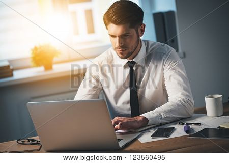 Expert at work. Top view of pensive young handsome man using his laptop while sitting at his working place