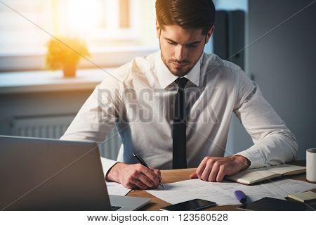 Time to sign some contracts. Pensive young handsome man signing documents while sitting at his working place