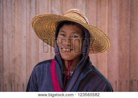 INLE LAKE MYANMAR - JANUARY 12 2016: Portrait burmese man a straw hat in local market. Inle lake Myanmar Burma