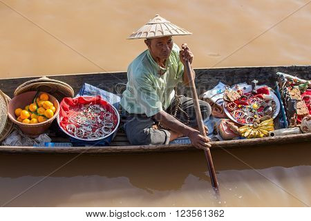 INLE LAKE MYANMAR - JANUARY 14 2016 : Unidentified Burmese man on small long wooden boat selling souvenirs trinkets and bijouterieat the floating market on Inle Lake Myanmar