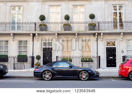LONDON UK - April 14: Luxury black Porsche. Houses in London english architecture