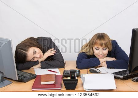 Two Young Office Worker Sleeping On Desk For Computers