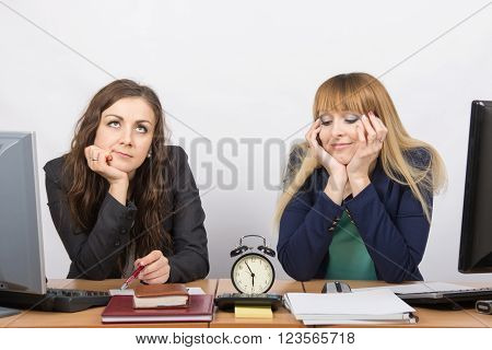 Two Employee In The Office Waiting For The End Of Working Hours On The Clock