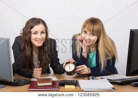 Two Girls In The Office With The Clock Happily Await The End Of The Working Day