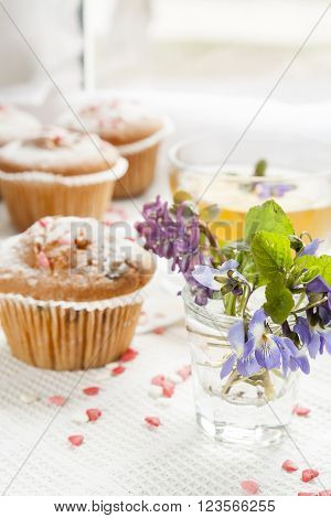 Blue spring flowers viola tasty muffins with sugar hearts and cup of green tea with lemon balm blue spring flowers viola on light background