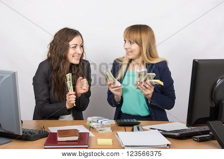 Two Very Happy Office Girl Happily Holding Wads Of Money In Their Hands