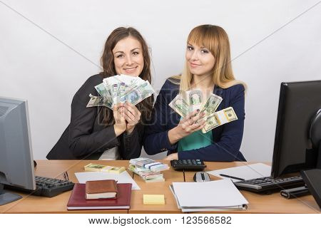 Two Happy Office Employee At A Table Holding A Fan Of Money Packs