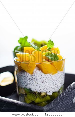 Dietetic dessert in the form of a fresh fruit salad with kiwi and peach with chia seeds and yoghurt served in a glass.