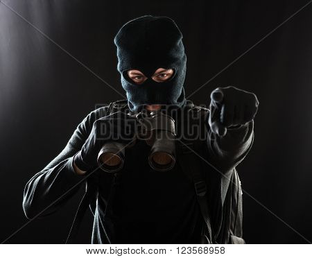 Thief in black clothes using binoculars and pointing his finger on the target