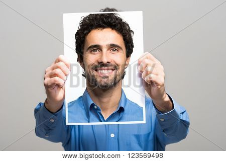 Portrait of a man holding a smiling image of himself