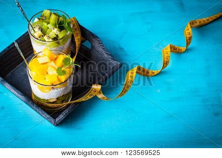 Dietetic dessert in the form of a fresh fruit salad with kiwi and peach with chia seeds and yoghurt served in a glass and lying tailor tape.