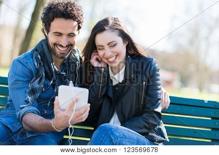 Couple listening music together while sitting in a park
