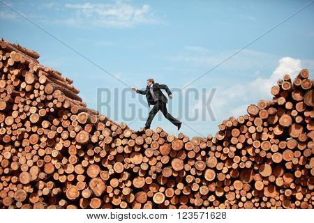 Metaphor - running business Man on his way to the  top of large pile of logs