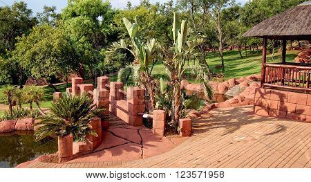 Zebra Lodge Gauteng Province South Africa - December 20 2012: Landscape in a park with palm trees a road from red brick and an arbor. Everything for your relaxation