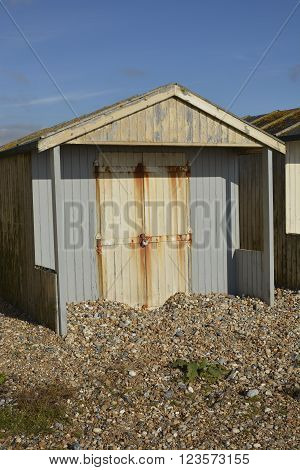 Wooden beach hut on shingle beach at Lancing Near Brighton West Sussex England. With shingle piled up against door after storm