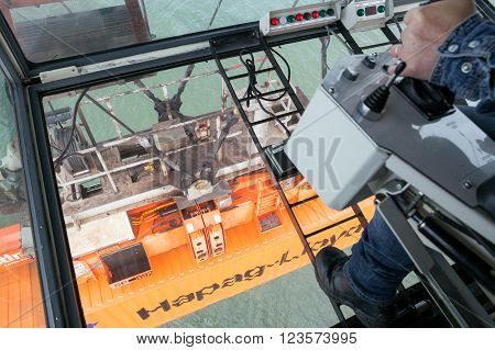ROTTERDAM - SEP 9 2015: Gantry crane operator moving a sea container in the Port of Rotterdam.