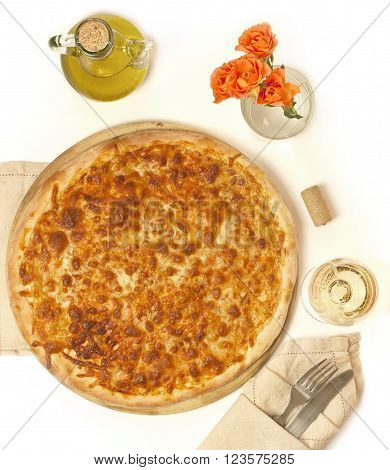 Photo of crunchy Margarita pizza on pizza stone with bottle of olive oil roses wine cork and glass of white wine with fork and knife wrapped in textile napkin shot from above on white background