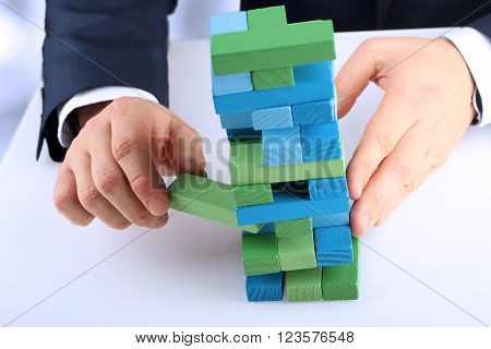 Planning risk and strategy in business businessman getting out a wooden block from a tower