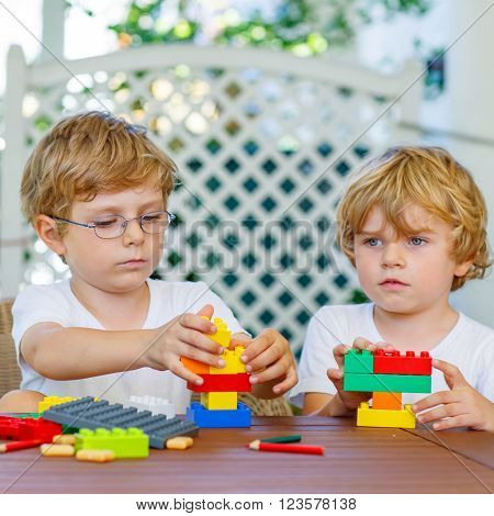 Two little blond friends playing with lots of colorful plastic blocks indoor. Active kid boys, siblings having fun with building and creating together.