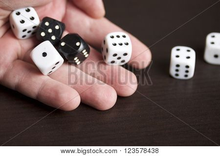 Dice in the hand of man. Throwing the dice during the game. Cubes of white and black color on a dark background.