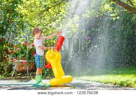 Active happy little kid boy  playing and splashing with a garden hose on hot and sunny summer day. Child having fun outdoors. Funny outdoors leisure wth water for children.