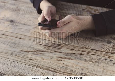 Close up of male hands holding smartphone and pointing finger to graph and text on screen at table wooden planks. Hipster style. Free space for text.