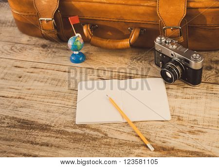 Suitcase, nootbook, pencil, flag, vintage camera on wooden planks. Aim, attainment, target, tourism, travel. At dawn. Hipster style. Top view with copy space. Free space for text.