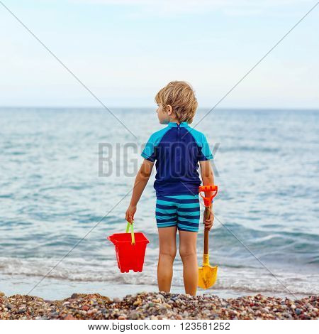 Adorable little blond kid boy standing on lonely ocean beach. Child playing with bucket and shovel and looking on horizon. Vacations, summer, travel concept. Preschooler enjoying summer vacations on sea.