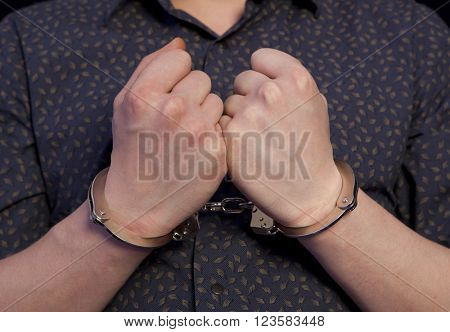 Hands of the prisoner. Arrested man in handcuffs