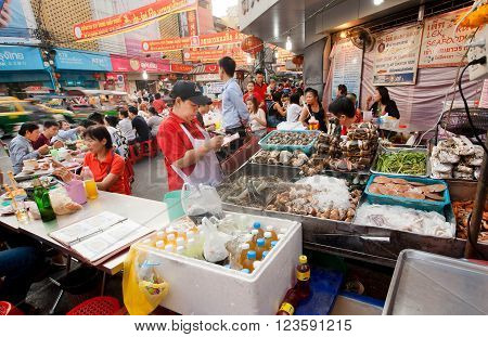 BANGKOK, THAILAND - FEB 14: Street trader of seafood market with shrimps brines fish and meat on February 14, 2016. Population of Bangkok is over 8 million most populous city of Thailand.